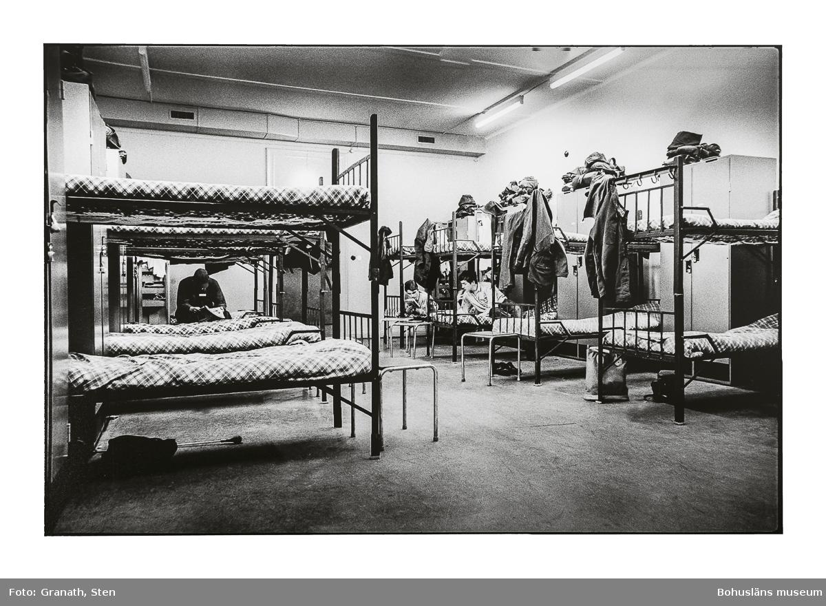 Sovsal på I17. I salen syns åtta våningssängar, samtliga slafar har täcken med rutiga påslakan. Mellan sängarna står skåp och på dessa ligger olika påsar och textilier. På krokar på sänggavlarna hänger kläder. I tre av sängarna sitter respektive ligger tre personer varav två läser.
