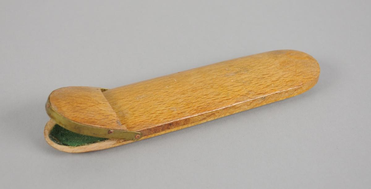 Avlangt brilleetui av tre med avrundene kanter. På den ene siden er det en metallkant rundt kanten, og denne enden kan åpnes.