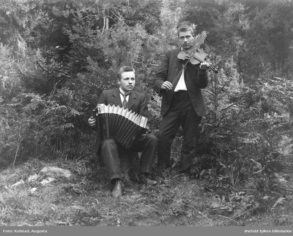 Gruppeportrett av to ukjente musikanter med enrader/trekkspill og fele /fiolin.