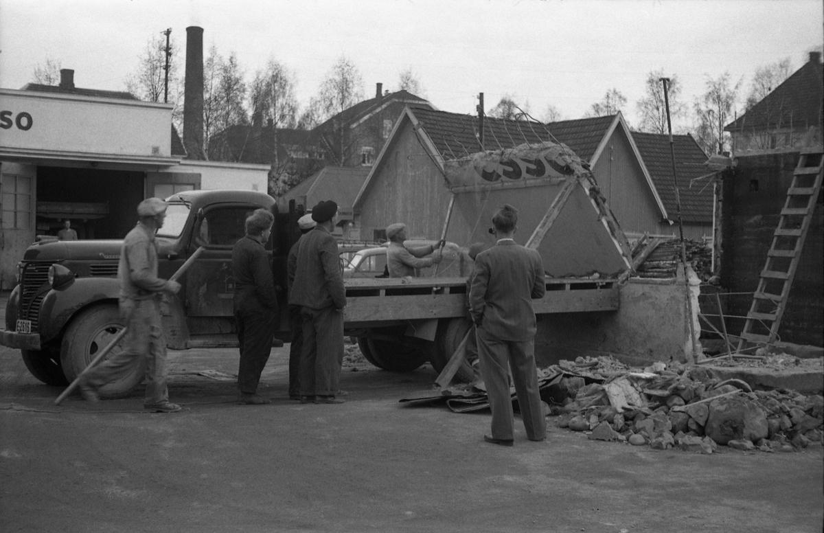 Lasting av rester etter riving av ekspedisjonsbua på Esso på Lena april/mai 1954. Rivinga hadde nok sammenheng med modernisering. Tre bilder. Ingen av personene på bildene er identifisert. Lastebilen er ifølge informant en Fargo 1946/1947-modell.