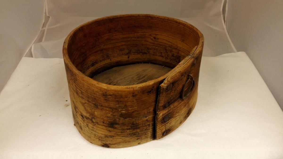 """Form: Uregelmessig rund. 1 mæle.  Mæle for maaling av korn - """"sognemæle"""" - laget av svöigd furutræs trysk, hvis skjöter er sammenbundet med jernsaum og en kjeng, hvori en ring av jern. Uregelmessig rund. Bunden indfældt i trysken og fastnaglet med trænagler.  Gave fra gaardbr. Torbjörn A. Haukaas, Kaupanger."""