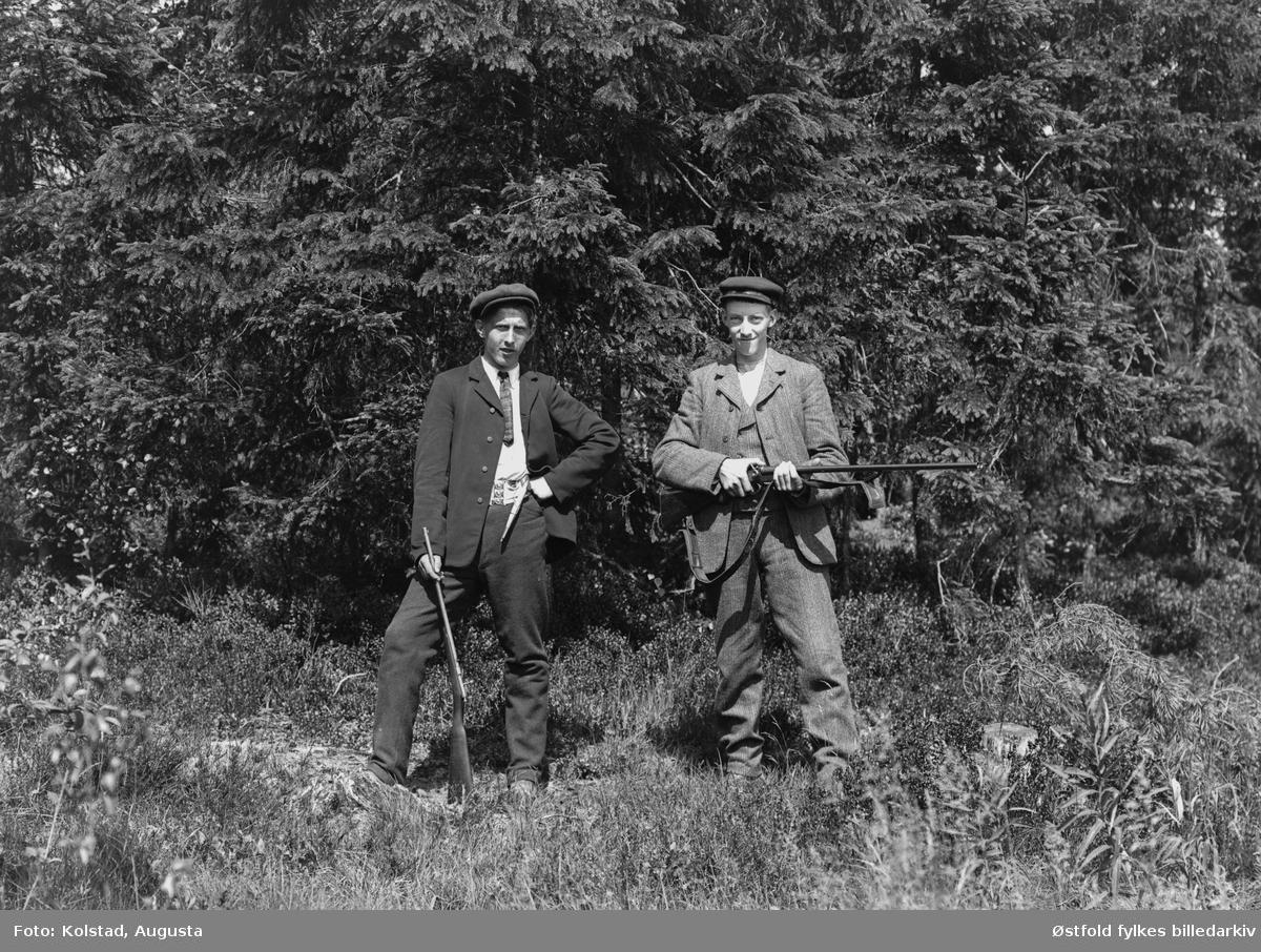 To jegere med våpen, ca. 1910-20, ukjente.  Karen til venstre har en fin tollekniv i beltet, mulig Totenkniv, kanskje det er bein i skaft og slire, vanskelig å si sikkert men materialet ser veldig lyst ut. I tillegg har han et finkalibret gevær, trolig kaliber .22, også kalt salongrifle.  Karen til høyre har et dobbeltløpet haglegevær, sideligger, med utenpåliggende haner. Brukes til fugl- og harejakt. Tor Ulsnæs 2018