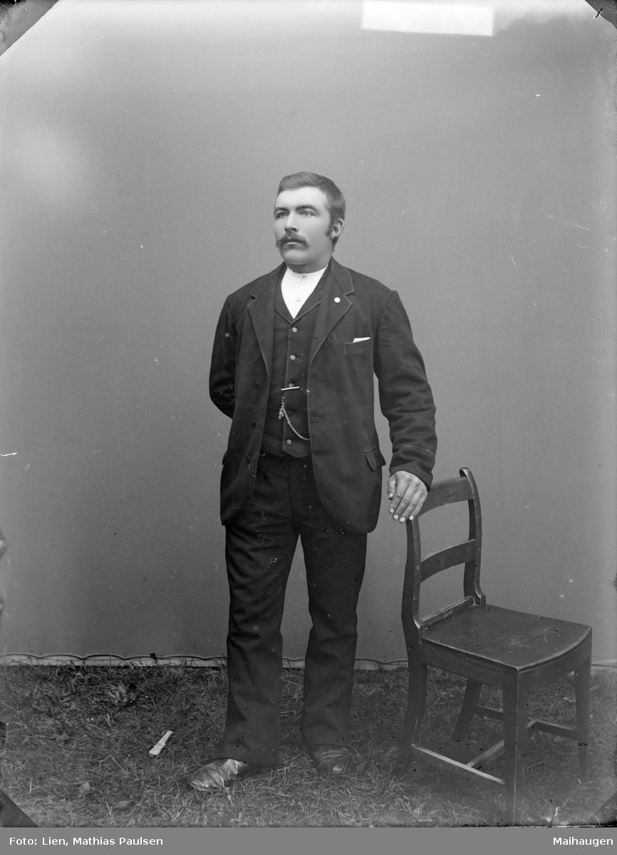 Mann med mørk dress og stol, atelierfoto.