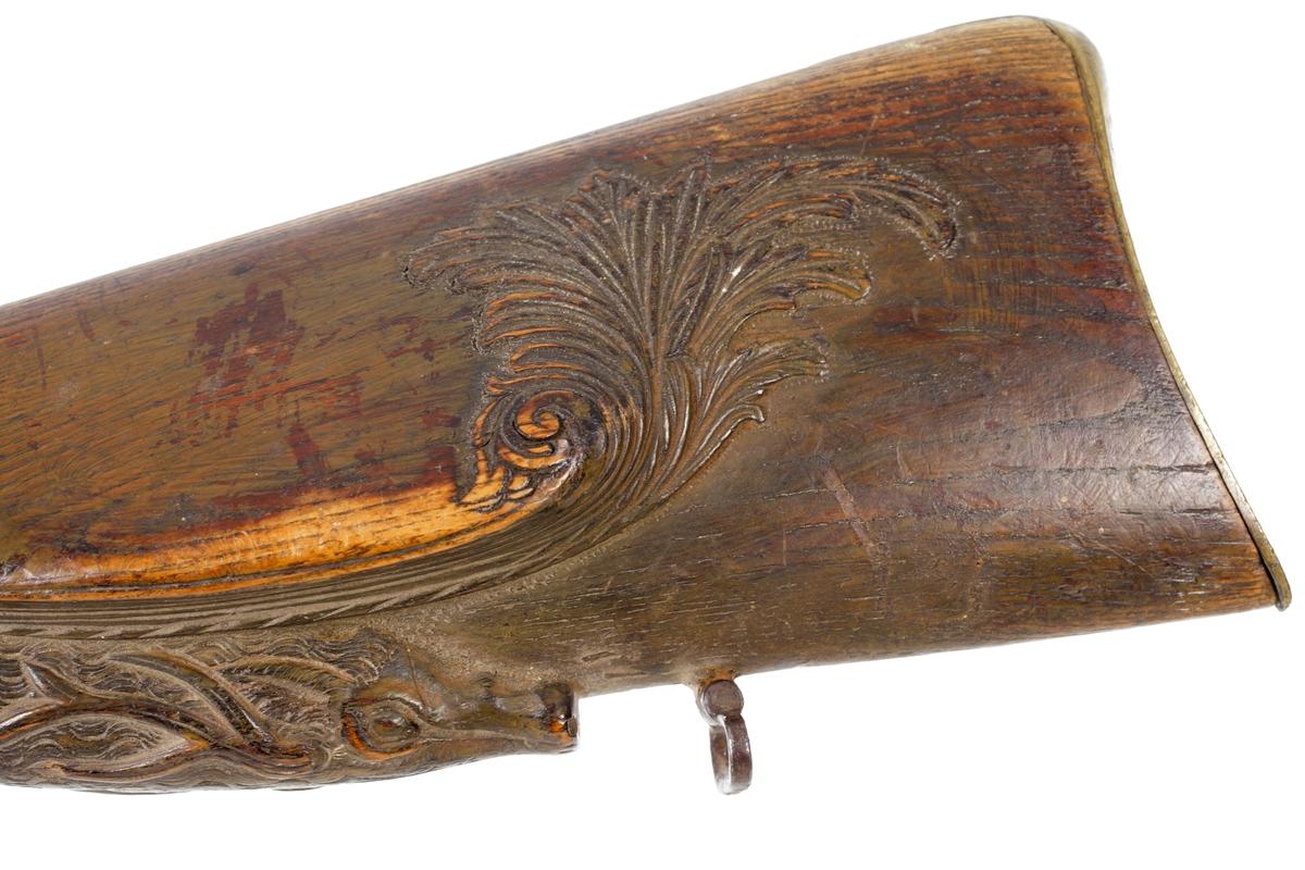 Jaktgevär med flintlås, sekundärt omändrad till slaglås och försett med helstock. Kolvhals och en bit på kolvens undersida är utförd som ett hjorthuvud med långa horn. Bakplåten av mässing går upp en bit på kolvens översida och avslutas med en spets. På framstockens undersida finns en laddstocksränna som har tre rörkor. Pipan är rund men övergår baktill i en åttakantig form. Bakom mynningen finns ett pålött korn. Varbygel och sidobleck är tillverkat av mässing, och lås samt pipa i stål. Pipan slätborrad med en innerdiameter på 16 mm. Inskrivet i huvudkatalog 1958.