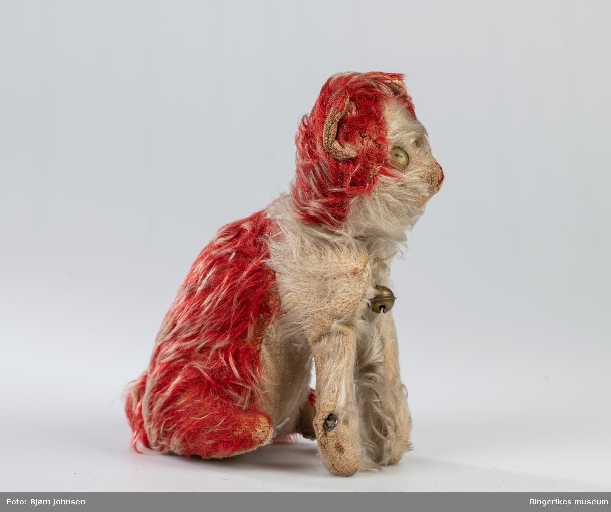 Fremstilling av katt i liten størrelse, men med trekk fra et kattedyr med ører, hale og snute. Stoppet og hodet kan dreies.  Sittende.  Typisk kosedyr for et lite barn.