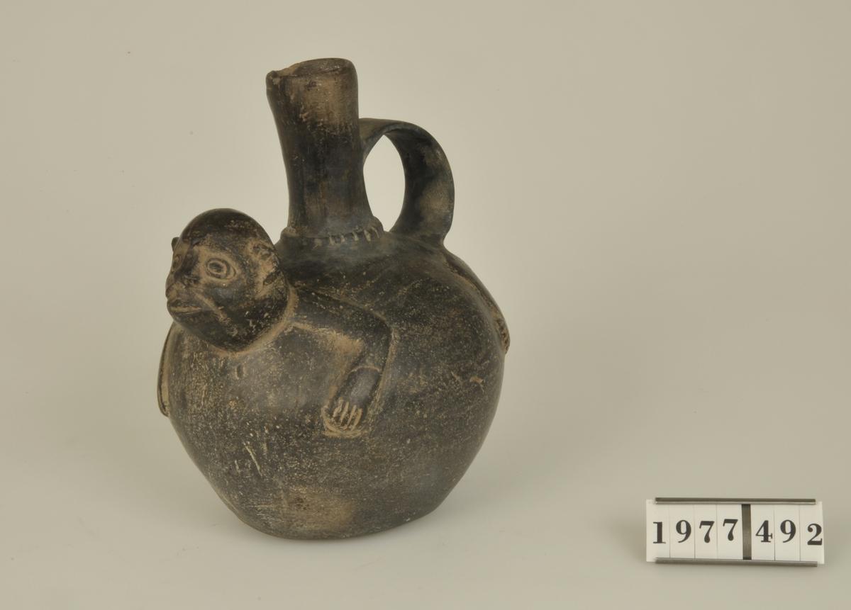 Svartglaserat gods. Kruset har en nästan klotformig kropp och en smal- c:a 6 cm hög - hals. På krusets framsida är ett aphuvud modellerat och längs överdelen framben, bakben och svans i relief.