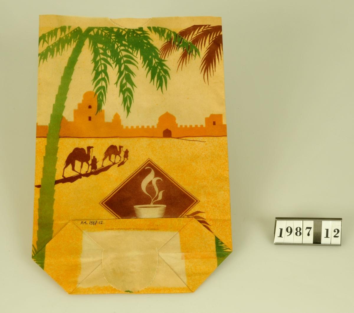 Tryckt motiv i gult, grönt och brunt, bl.a. kaffekopp, palmer och kameler.  Kommer från livsmedelsaffären Oskar Nilssons Eftr:: Lärkvägen 15, Alingsås. Affären etablerades 1906 och lades ned i juni 1986. Kaffepåsar tillvaratagna av B.S. då hon 1973 övertog affären (Oskar Nilssons)