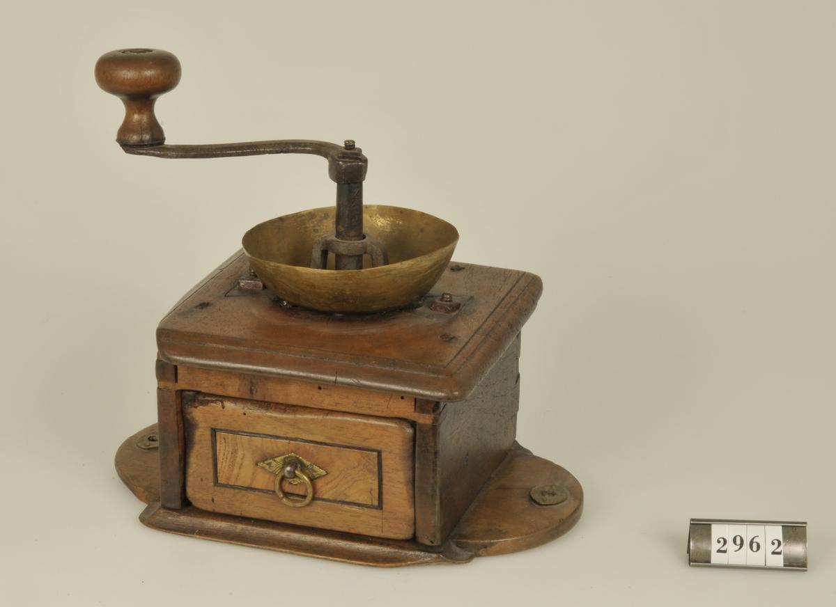 Inom fyrkantigt träställ med låda för det malda kaffet.   Kvarnen inköpt av givaren i Lena sn, Vg.