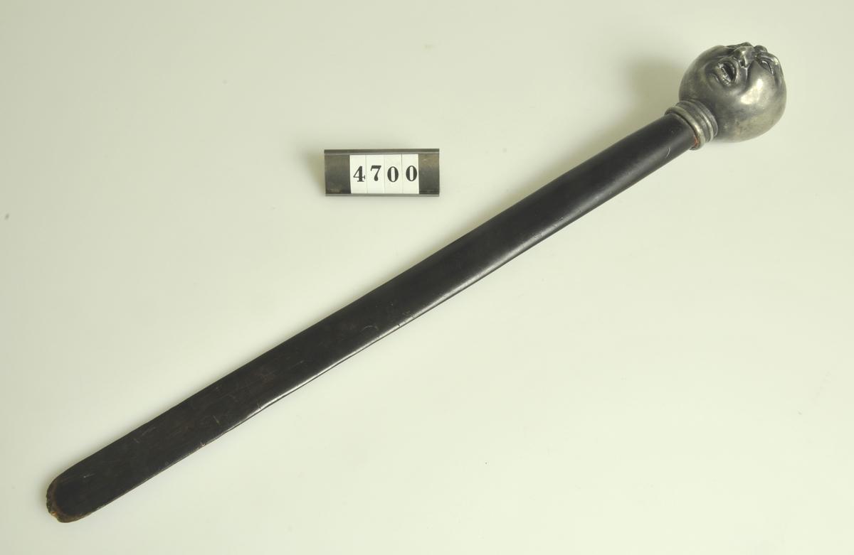 Med blad av trä och skaft av tenn i form av ett människohuvud.  Tillförd samlingarna före år 1961.