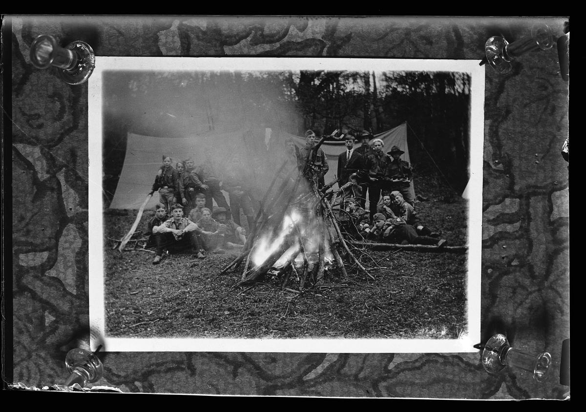 """Reprofotografi av foto föreställande ett antal unga pojkscouter runt en eld. I bakgrunden syns två tält. I fotografens anteckningar står det """"Rep. för Ekendahl""""."""