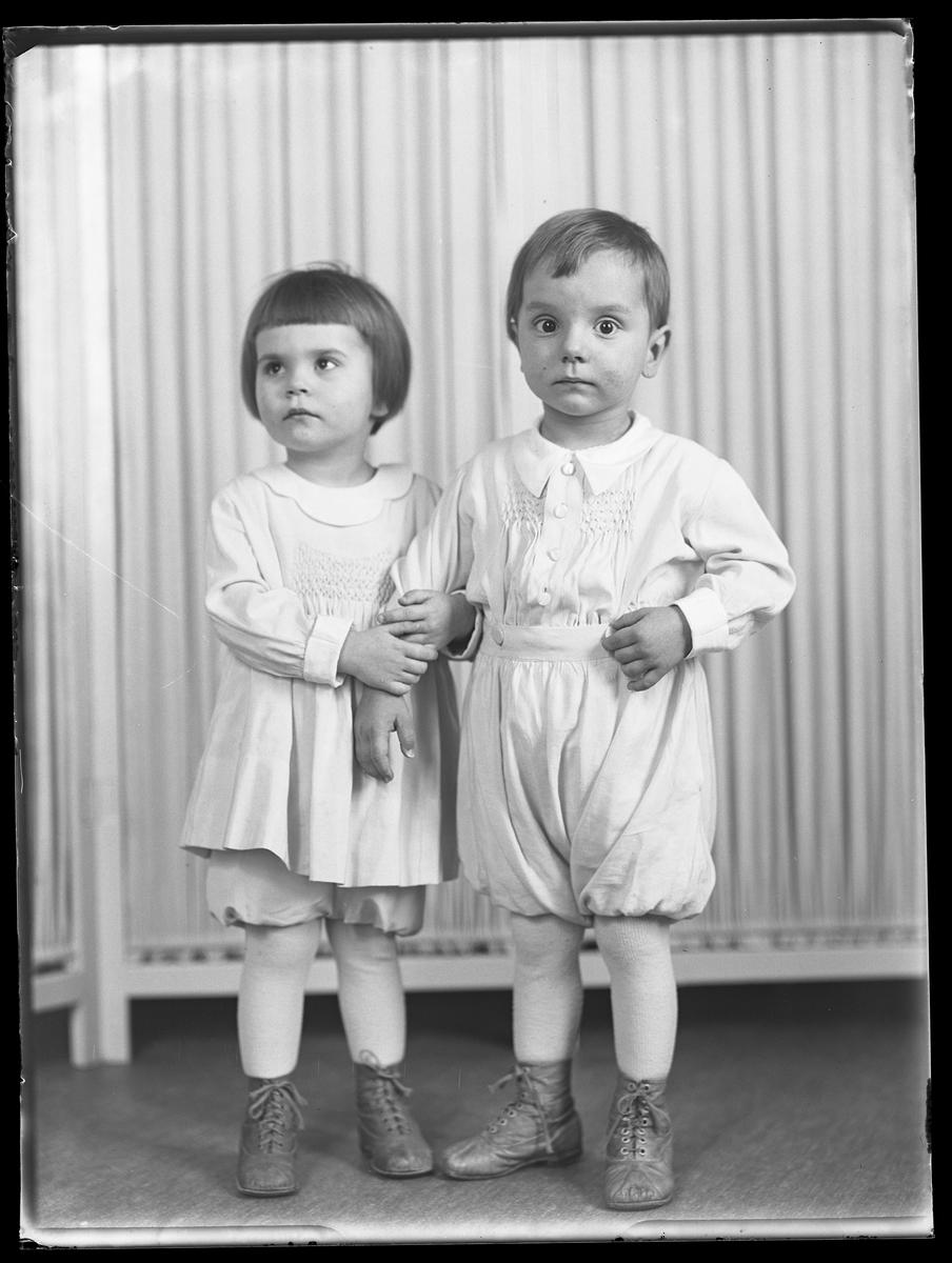 """En flicka står och håller i sin brors arm. I fotografens anteckningar står det """"Ing.[enjör] Bergs barn"""", tolkat som tvillingarna Peter Wilhelm och Ulla Maria."""
