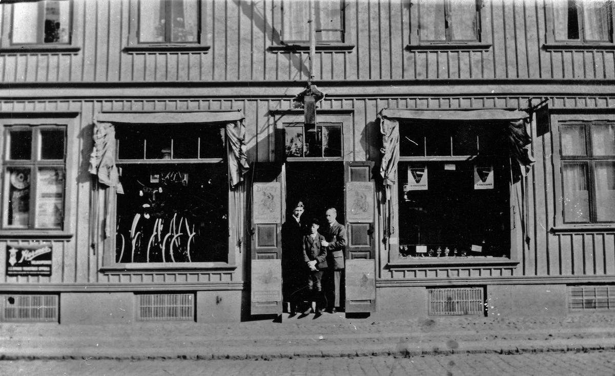 Två män och en pojke i ingången till Fritz Johanssons Cykelaffär. Kungsgatan. Kvarteret Enigheten.