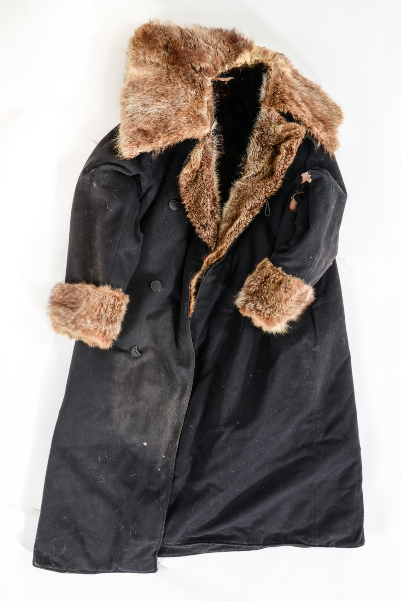 Frakk, kjørepels i svart ulltøy, fóra inni med svart bjørneskinn, ermane er også fòra med bjørneskinn. Ulveskinn(?) på kragen, slaga og rundt ermane.  Tre knappar og hempe på kvar side i opninga. Ein knapp til å halda saman kragen med.