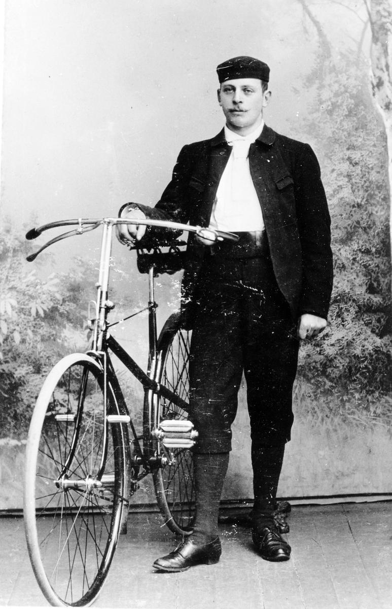 Man med knickers och mössa står bredvid en cykel i en fotostudio.