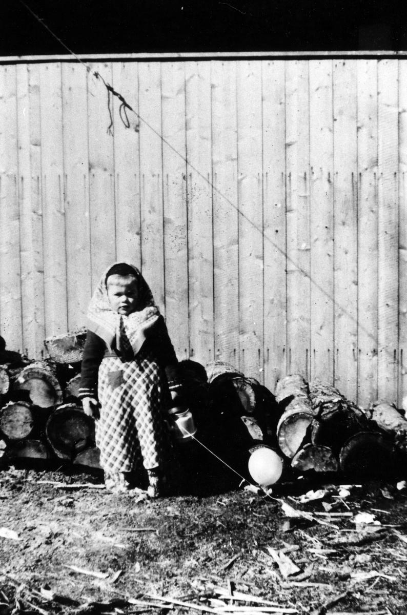 En liten påskkärring står vid ett staket med vedklabbar strax bakom sig. Bilden är tagen i kv. Storken, Nygatan 11. På platsen låg sedan Tempo.