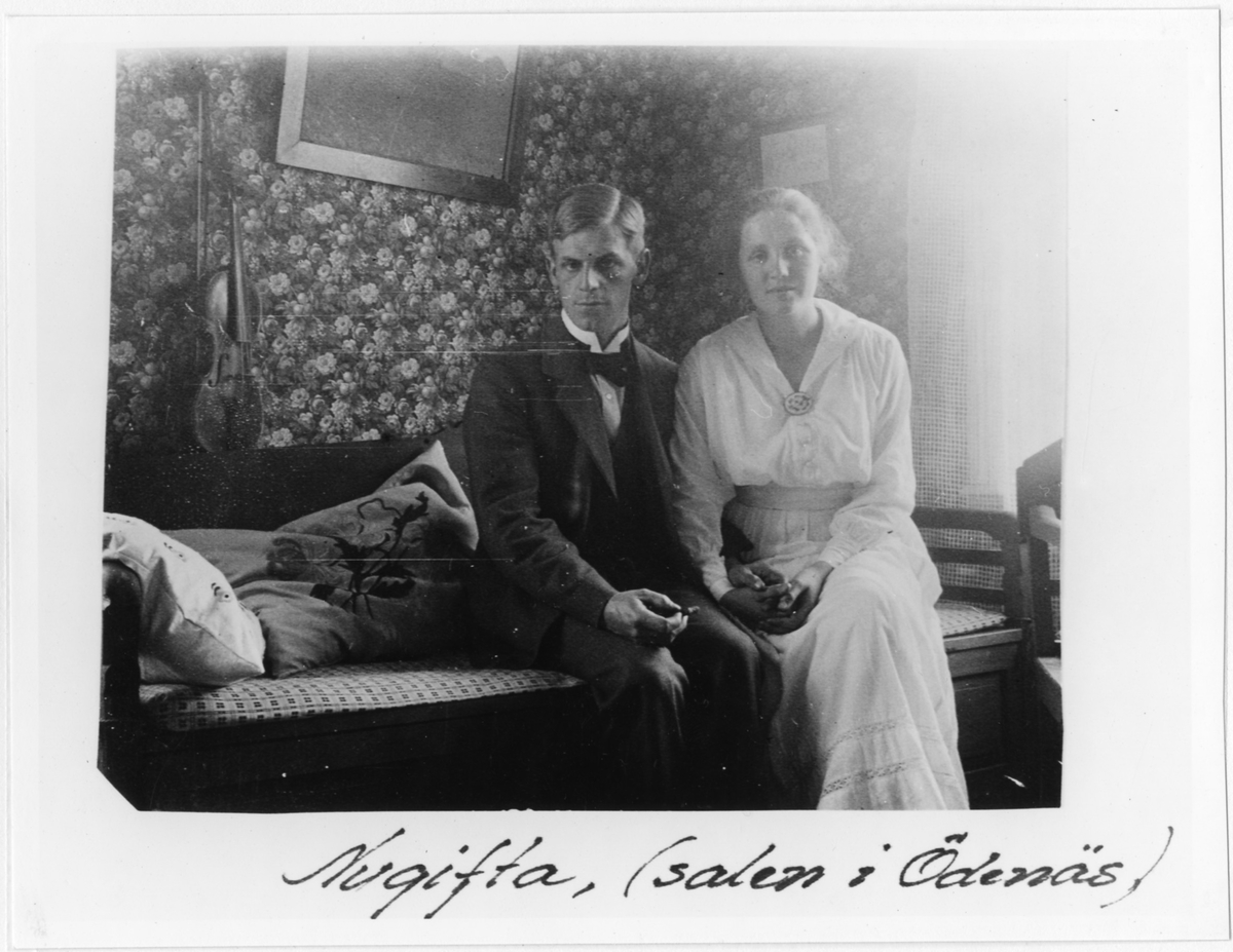 Nils och Elisabeth Henning sitter som nygifta på en soffa i hemmet på skolan i Ödenäs. Bilden är tagen i salen i Ödenäs.  Nils Henning var lärare i Ödenäs från 1915 och familjen bodde i skolan.