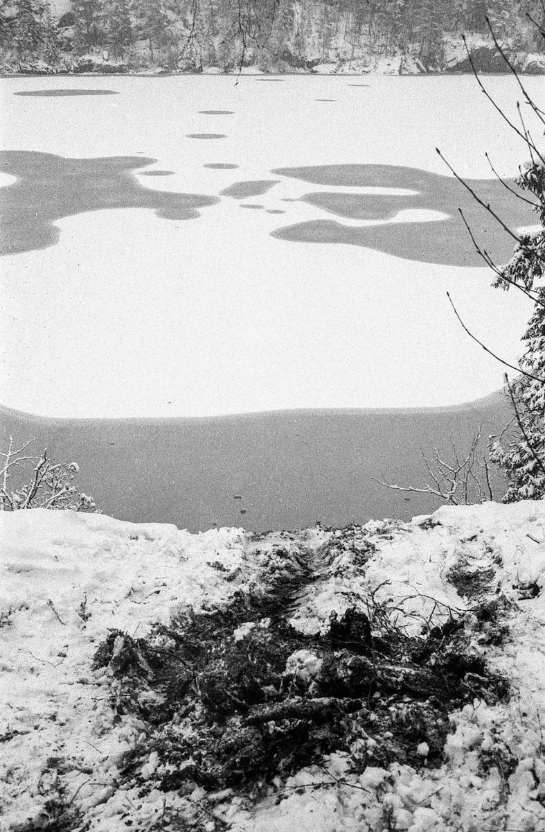 Bildumping i Gjersjøen. Snø og slaps. Bilvrak blir dratt opp med kranbil på lasteplan. Gjersjøen i bakgrunnen.
