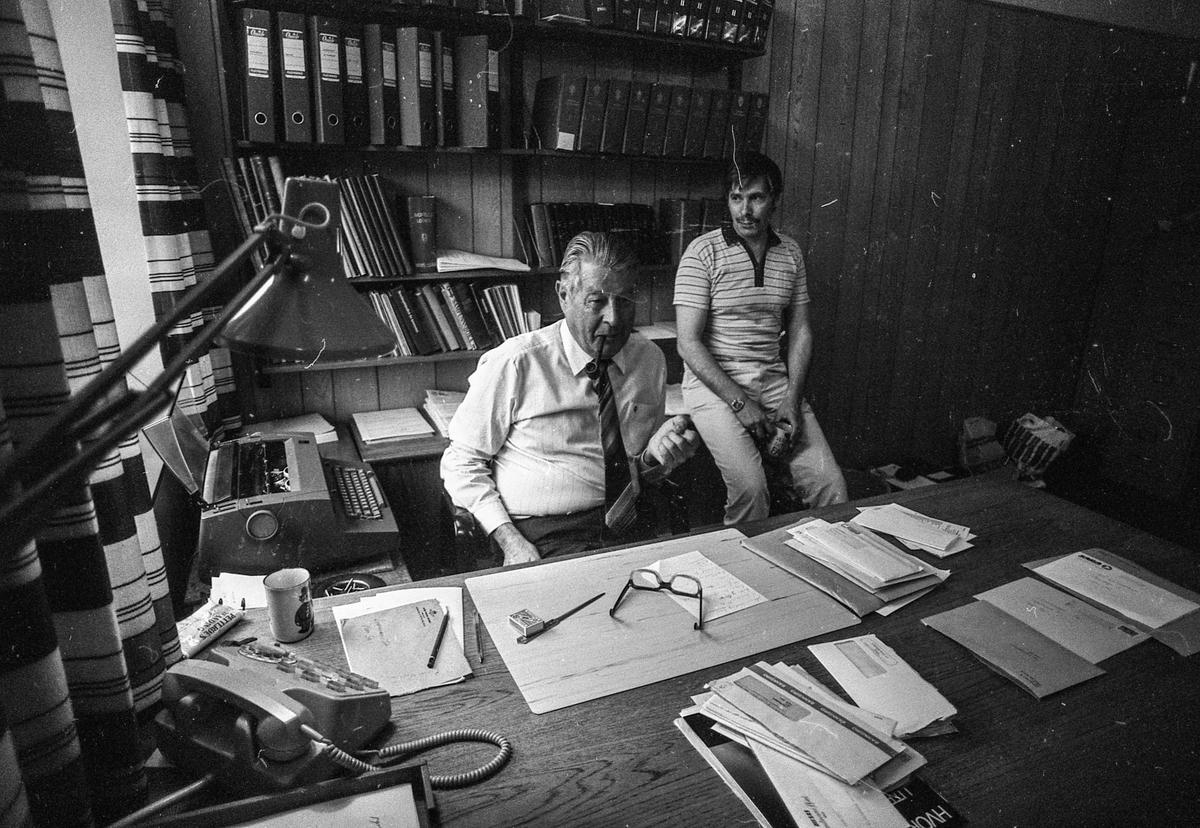 Ski lensmannskontor, tillitsmann Arne Schei sitter ved bordet, mange politimenn bak ham. Lensmann Odd Aamodt, mye papirer og hyller bak.