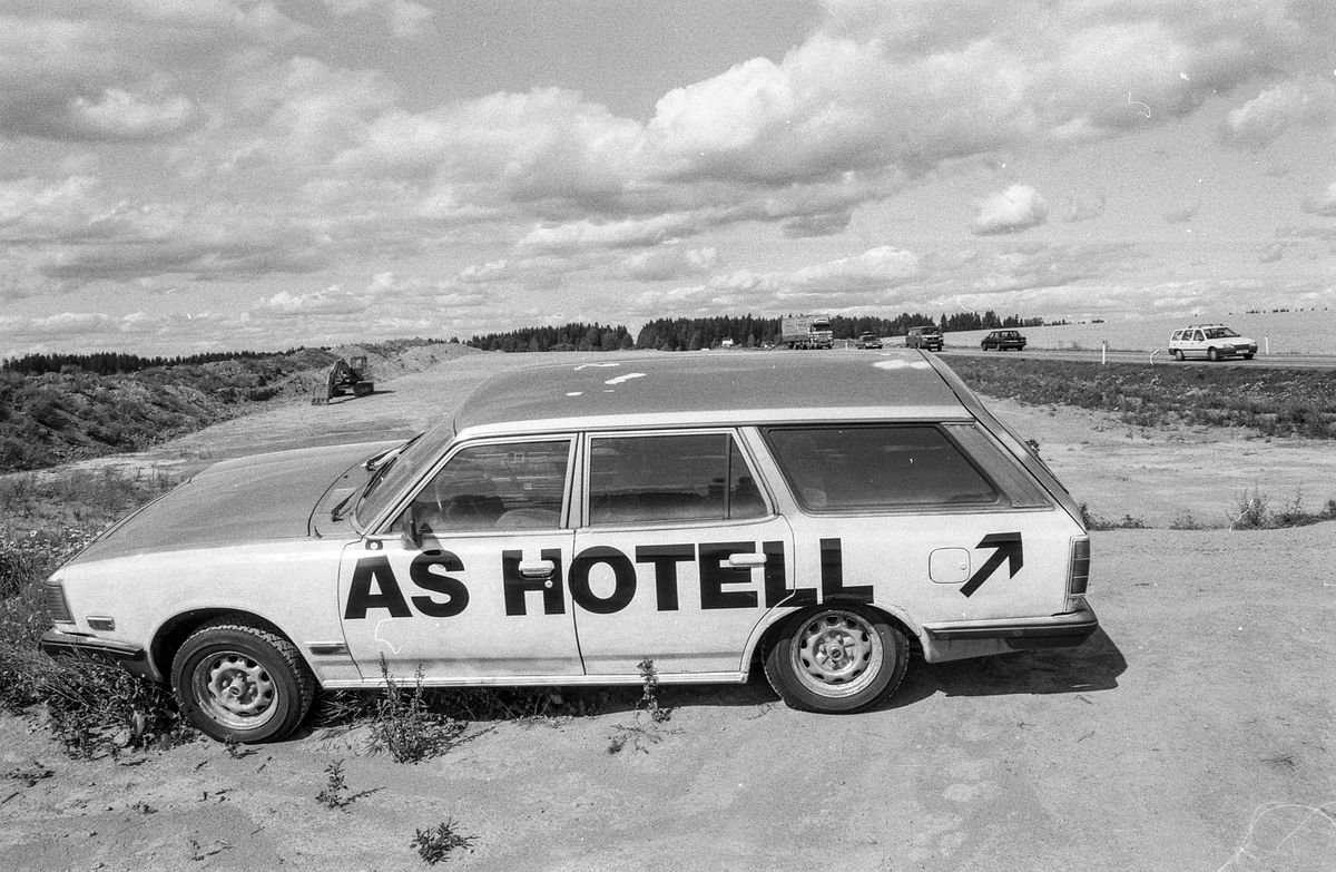 Biler påmalt reklame for Vestby Hotell parkert på et jorde.