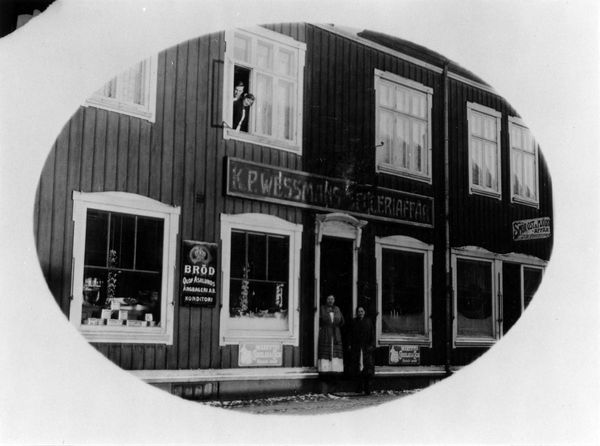 Vinklad gatuvy av KP Wessmans speceriaffär. På husets träfasad finns 5 olika skyltar, varav 2 är reklam för Mazzetti choklad och cacao. I dörröppningen står 2 kvinnor och i ovanvåningens vänstra fönster ses en man och en kvinna.