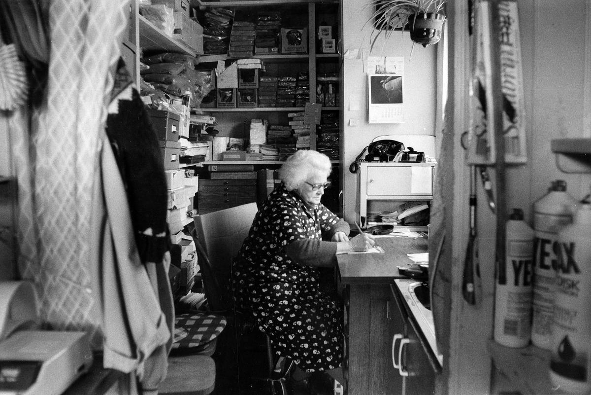 Bild från Doris Kiosk & Specerier. En äldre kvinna sitter och skriver vid ett skrivbord, troligtvis speceriaffärens kontor.