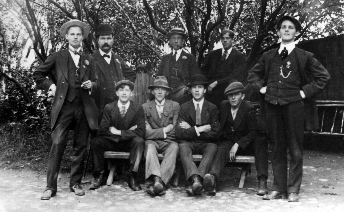 Gruppbild på en samling Alingsåsare omkring 1900. Gruppeb består av nio män som samlat vid en parkbänk.