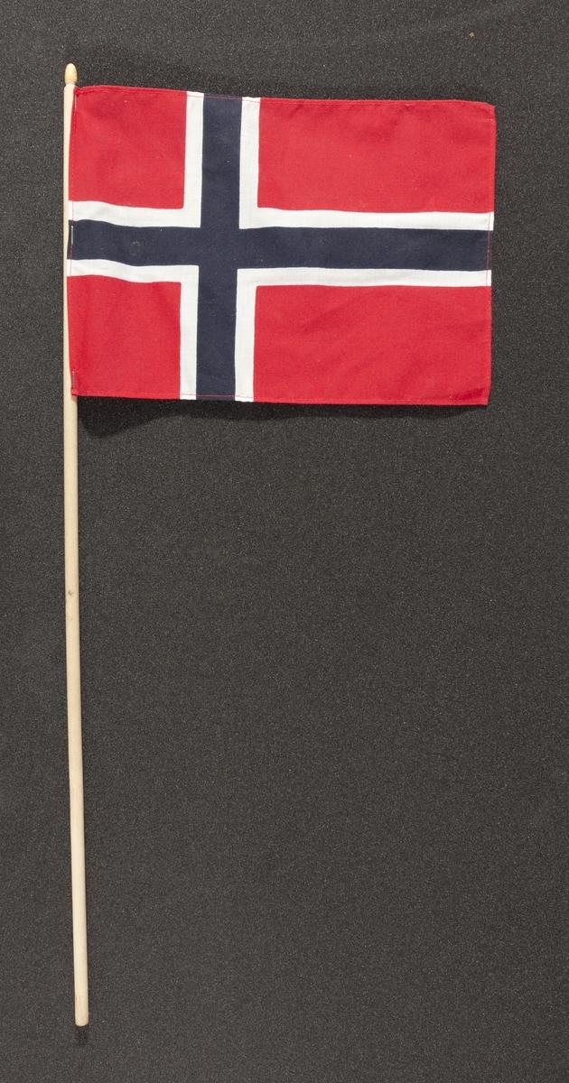 """Flagg innsamlet etter terrorhandlingen 22. juli 2011 fra minnesmarkeringene i Lillestrøm.   Klassisk norsk flagg slik vi kjenner det fra 17.mai feiringer: Blått kors i midten, hvitt kors som """"omkranser"""" det blå (litt tynnere fargefelt) på en rød bakgrunn, de blå og hvite korsene går helt til kanten av flagget. Dimensjonene på feltene er slik at de to røde felten mot pinnen er halvparten så store som de to ytterste røde feltene. Flagget brukes av både barn og voksne.Tuppen på pinnen som flagget er stiftet på, er malt med gullfarge, men den er nokså avskallet. Pinnen og flagget er blitt litt misfarget av opphold utendørs. Sømmene på flagget er røde."""