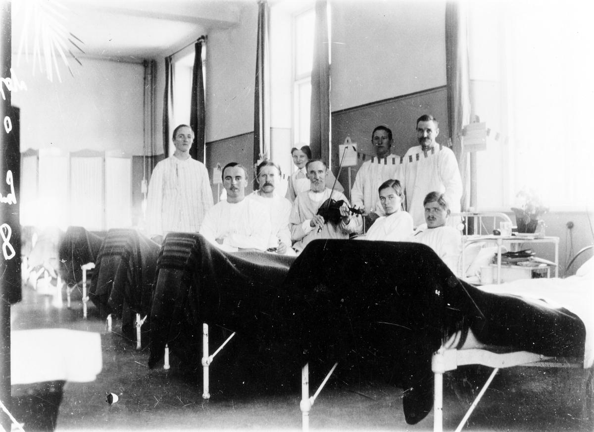 Bild tagen inifrån en sjuksal på Alingsås lasarett med 8 manliga patienter och en kvinnlig sjuksköterska. Mannen mad fiolen i mitten är Johannes Eriksson, pappa till fotografen Teodor Eriksson.