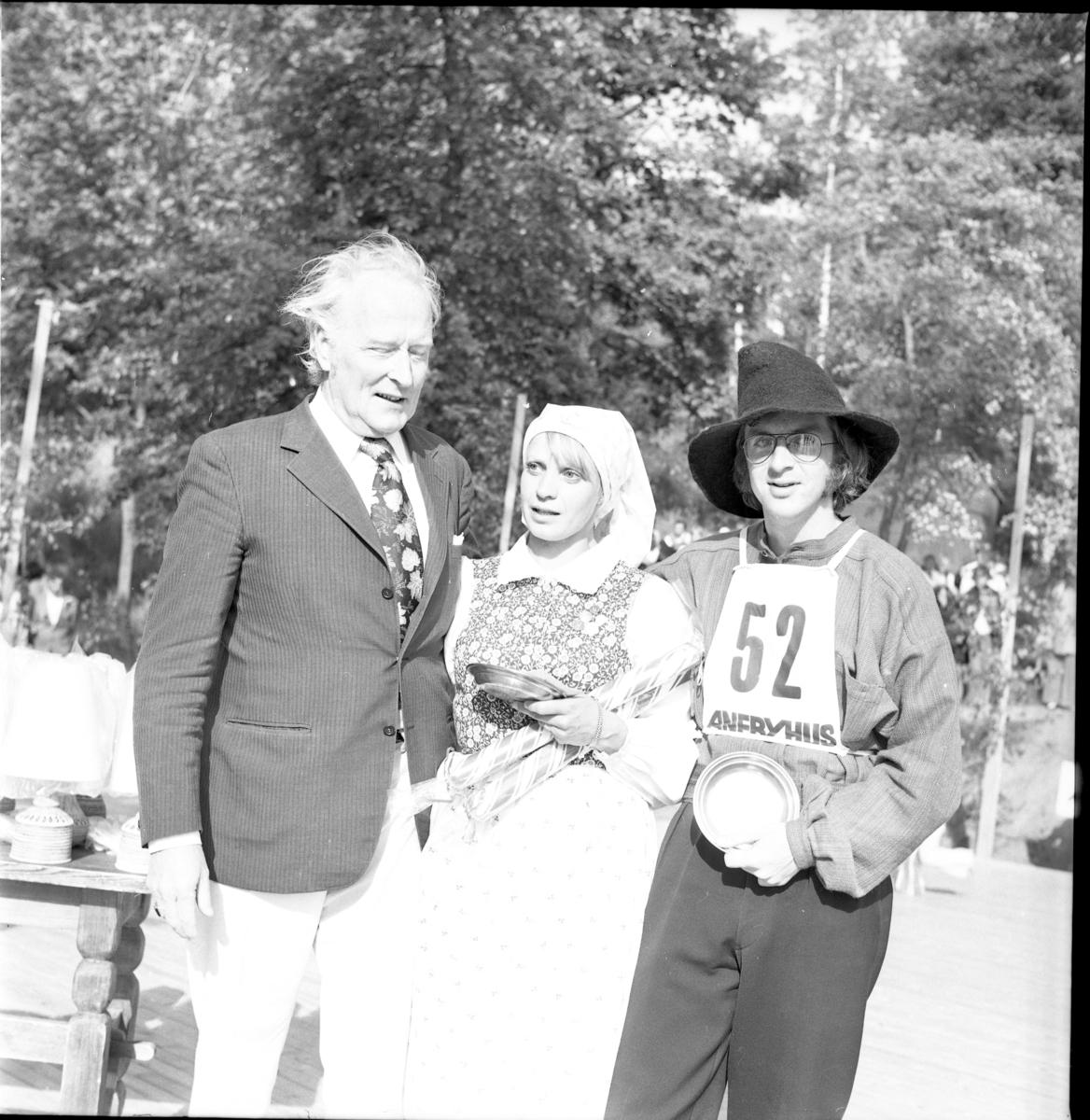 Grännapolkan på Grännaberget, 1975. Danspar nr 52, troligen segrarna Gunnel Johansson och Ola Holmberg från Uppsala intill man som troligen är prisutdelare. Dansparet har tennfat och stor polkagris i famnen.