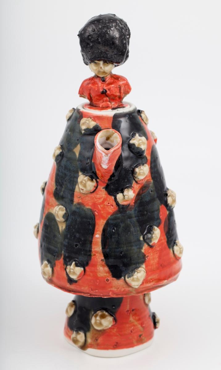 Rød kanne dekorert med hoder med hodeplaggene til britiske gardister fra regimentet Irish Guards i den britiske hæren. Kannen har stor hank og lokk med en liten gardist i rød uniform og samme hodeplagg som de andre.