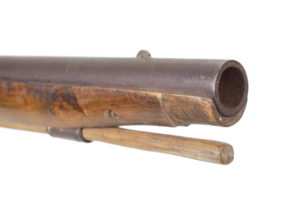 Jaktgevär med flintlås, sekundärt ombyggt till slaglås. Helstockat med näsbleck. Laddstocken sitter i en laddstocksränna med tre rörkor. Framstock och kolvhals nätskurna på sidorna. Kolven har ett kindstöd samt en bakplåt av ytbehandlat järn. Pipan är rund med en åttakantig avslutning. Siktet är utfilat vid svansskruven och det finns ett korn 45 mm. bakom mynningen. Främre rembygel sitter vid mellanrörkan, och den bakre remfästet sitter skruvat i kolvens underkant. Pipan slätborrad med en innerdiameter på 15 mm. Inskrivet i huvudkatalog 1904.