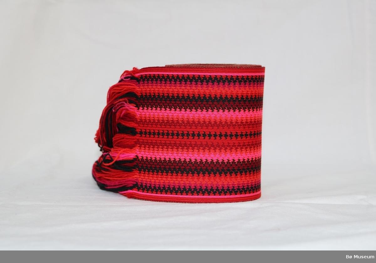 Stakkebelte med tafs i eine enden og mønster som består av striper og sikksakk-mønster. Type: Hælge Beltevevarbelte.