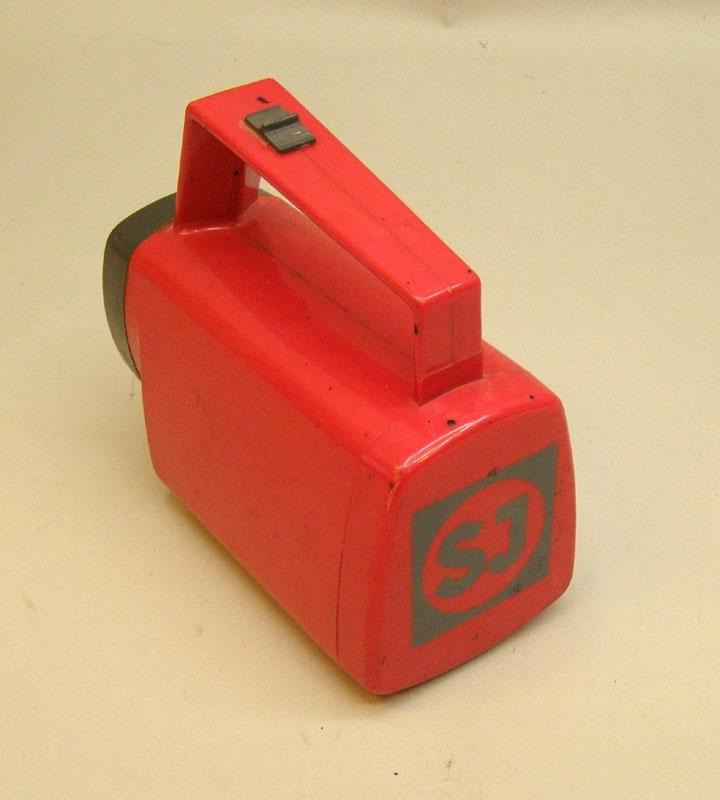 """""""Standardficklampa"""" av röd plast med SJ-märkning i bakre änden.  Historik: Ficklampor av denna typ användes av SJ:s personal på expeditioner och lokförarhytter m.m, från ca 1980-talet  och fram till åtminstone 2008."""