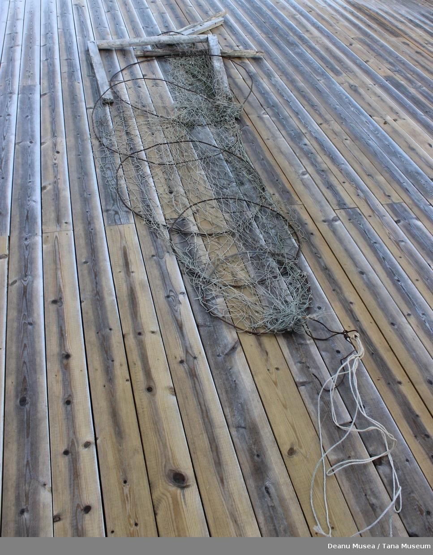 Ruse brukt i seidastryke med stengselet på 1950-60 tallet. Garnet i rusen er av nylon, ett matrialet som ble tatt i bruk av garnfiskerene i Tana i denne perioden. Rammen av tre.