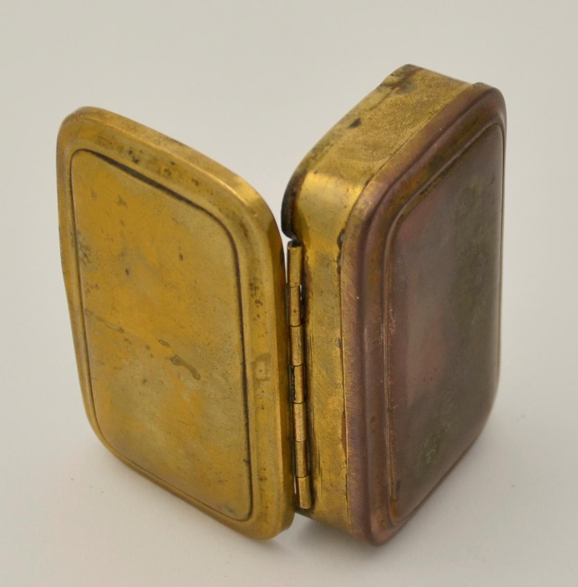Tobakksdåse. Metall. Rektangelforma øskje med påhengsla lok på begge sider. Spegel under eine loket. Gulleg utanpå, utan eine sida som er raudleg. Sølvfarga inni.