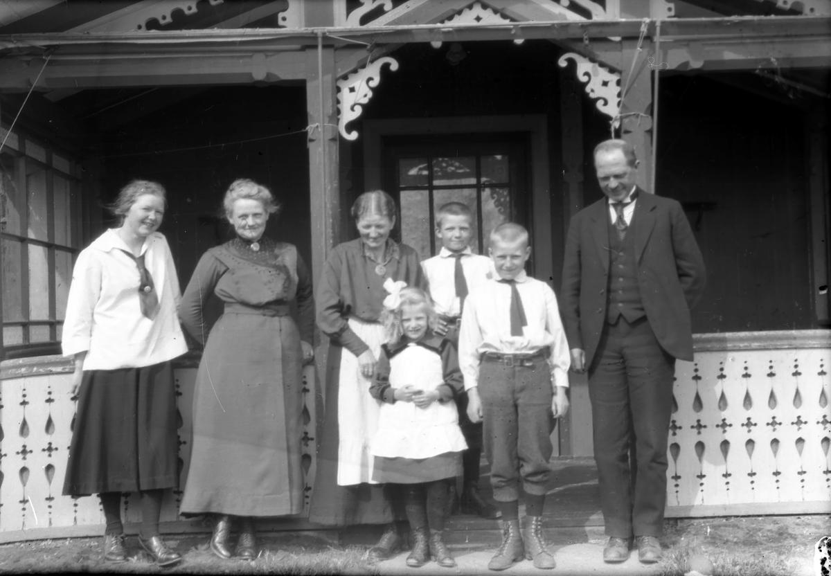 Mann,kvinner og barn foran veranda/inngang.