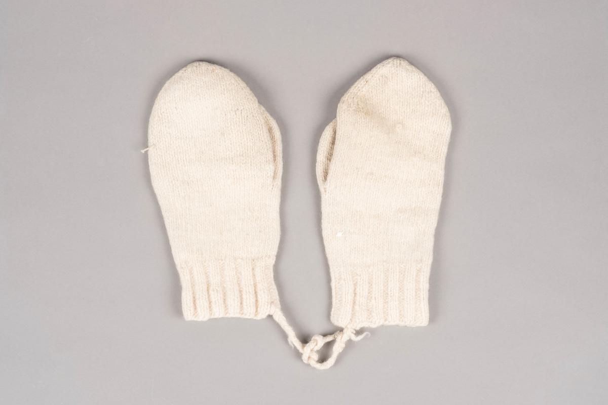 Ett par strikket votter. Vottene er strikket i hvitt garn. Hver vott har en strikket snor fra åpningskanten. Snorene brukes til å knyte vottene sammen når de ikke er i bruk. Høyre votten har brodert fangenummer (15942). Det ser ut som den venstre votten har det samme fangenummeret, men det eneste tallet som er synlig er 2, resten har raknet opp.
