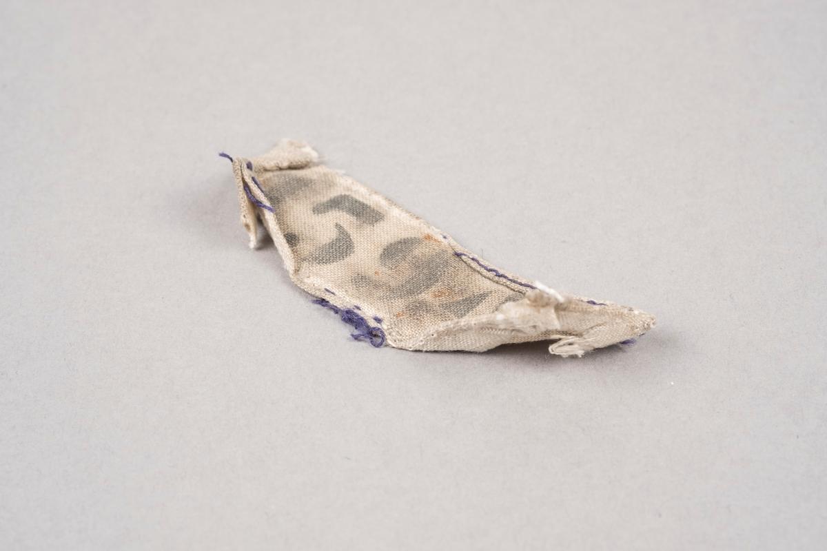 Merkelapp i naturhvitt lerretsstoff med nummeret 15942 trykket på med sort blekk. Merkelappen har søm av mørk blå tråd på kantene. Deler av tråden er raknet. Merkelappen er svært misfarget.
