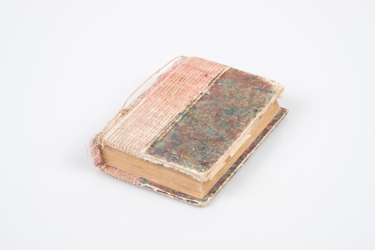 Liten minnebok med omslag i papp med marmorert mønster i rødt og blått. Sannsynligvis laget på bokbinderiet. Boken er sydd sammen med rosa tråd, og det kan virke som om ryggen har falt av, noe som gjør at konstruksjonen av boken kommer frem. Det er signaturer og hilsener fra fanger i boken.