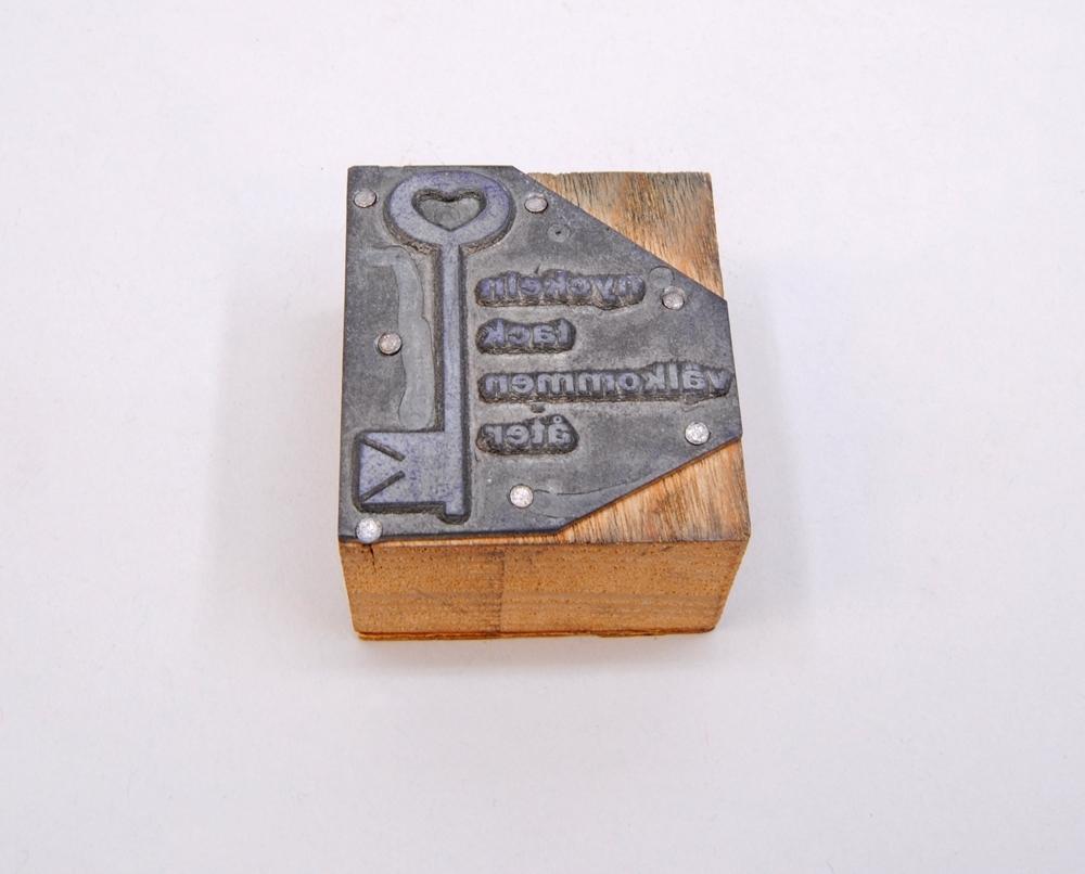 """Rektangulär kliché av grå metall monterad på en träkloss. Den övre och nedre kanterna på höger sida är beskurna, På Finns en nyckel med ett hjärta i den övre öglan, i relief. Bredvid finns texten: """"nyckeln tack välkommen åter"""", i relief.   På undersidan av träklossen finns märkningen: """"4."""", skriven med blyerts."""