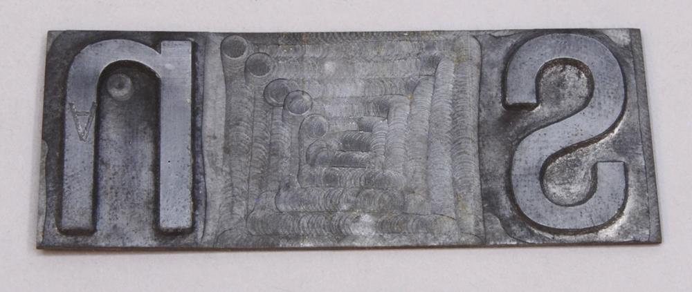 """Rektangulär kliché av silverfärgad metall. Från höger finns bokstäverna """"s"""" och """"n"""" i relief. Mellan bokstäverna finns mellanrum."""