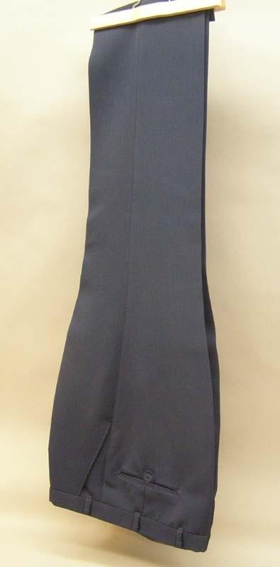 """Mörkblå byxor i kraftig textil med struktur, storlek 54. Gylf med dragkedja och knäppning med hake. Två stycken fickor framtill och en bakficka med knäppning med mörkblå plastknapp. På en tillverka lapp i linningen står tryckt: """"UNI-teco. Made in Sweden""""."""
