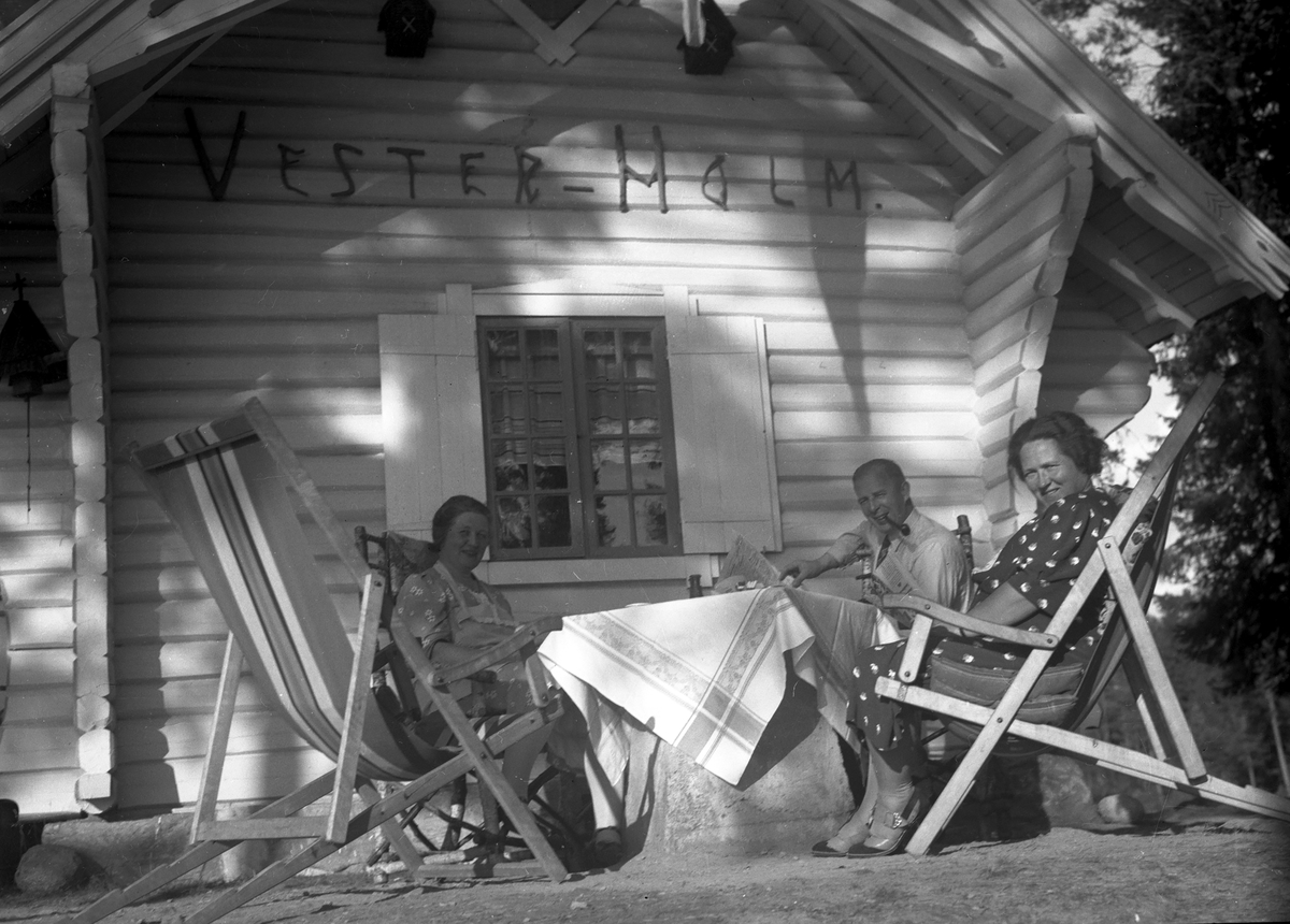 Mennesker sitter ved tømmerhus,Vester-Holm