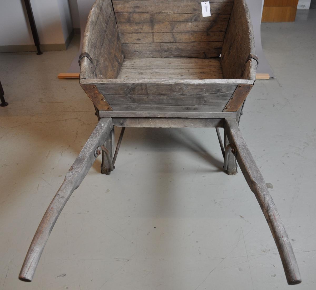 Trillebår av tre og jern. Trillebåren har en ett hjul med påfestet ring av jern, to håndtak og to støttebein. Kassen har utbøyde og avrundede sideplater. I hjørnene av kassen er det armeringer av jern.