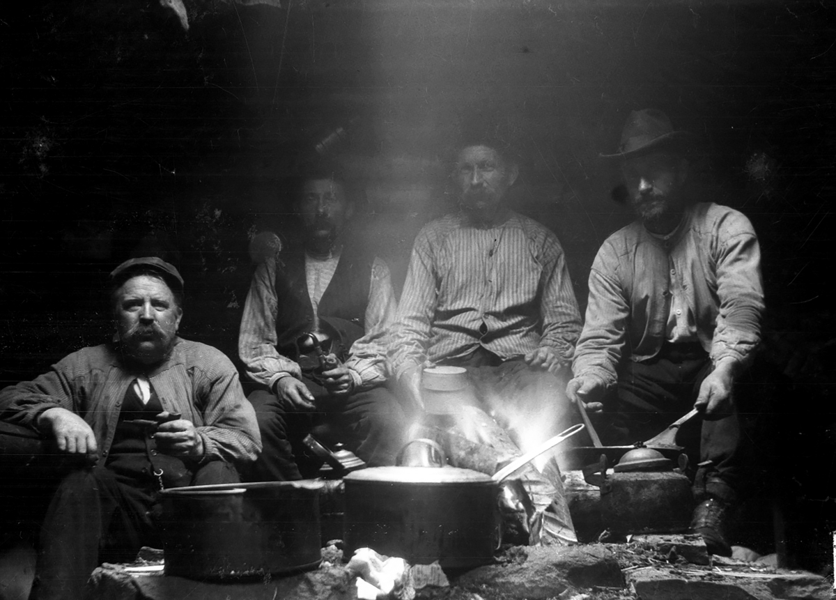 Fire menn ved bål i koie (skogsarbeidere).
