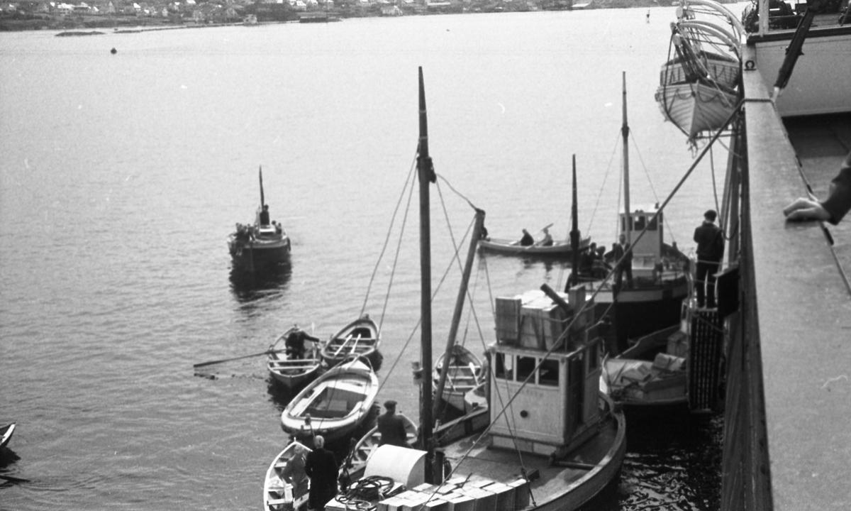 Båter i forskjellige størrelser langs skipssiden. Suderøy på vei til fangstfeltet.