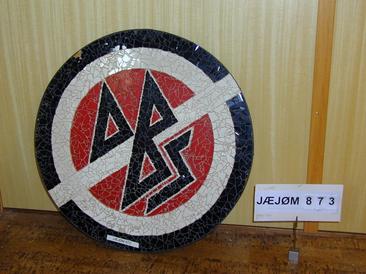 Rundt skilt utført i mosaikk med DBS sin første logo.