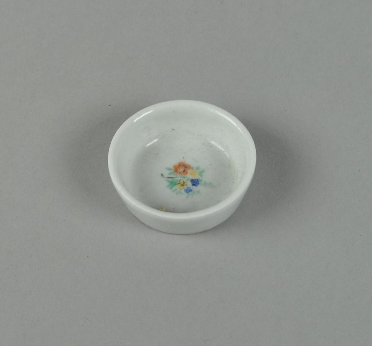 Bolle av glassert keramikk, med malte blomster i bunnen.