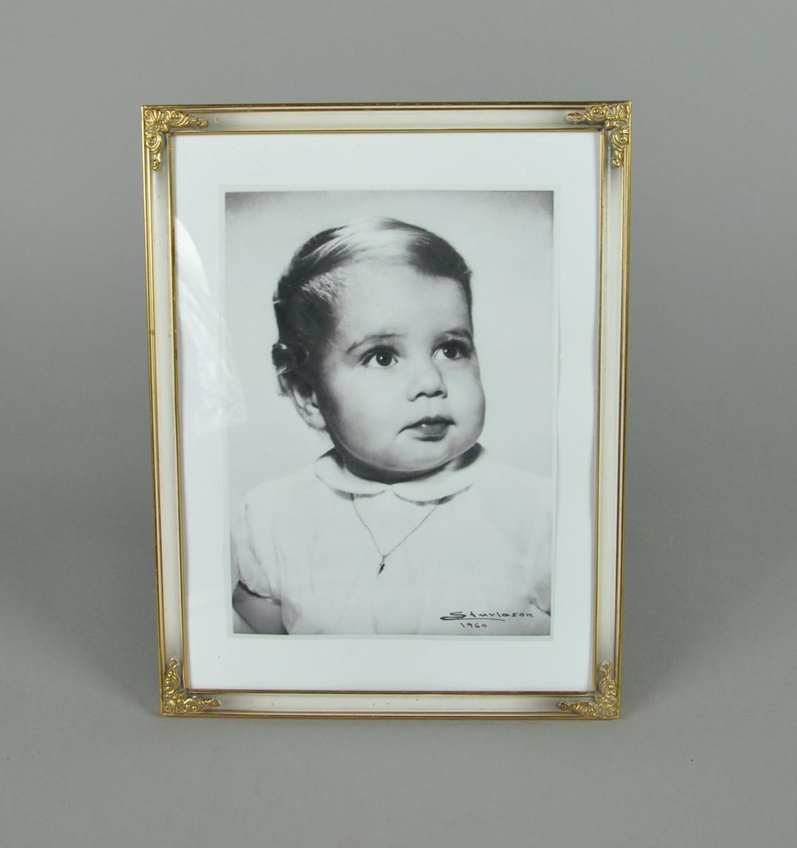 Stående portrettfotografi av Anita Henriksen. Ramme av metall med gullforgylt dekor. Bildet er en kopi.