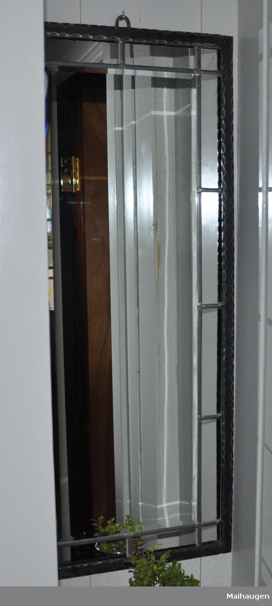 Speil med ramme av metall. Speilet er oppstående rektangulært og har sprosser med 16 speilpartier ved kanten. Speilrammen har dekorative innfellinger av halvsirkler, og hempe på toppen.